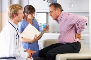Male Patient Visiting Doctor's Office With Back Ache